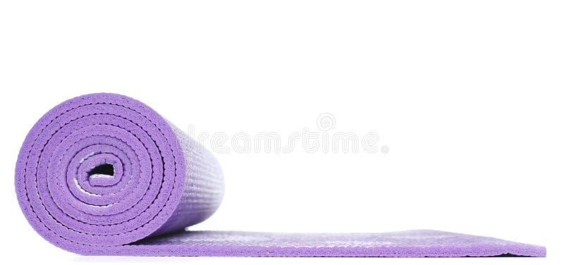 Фиолетовая циновка йоги в белой предпосылке стоковые фото