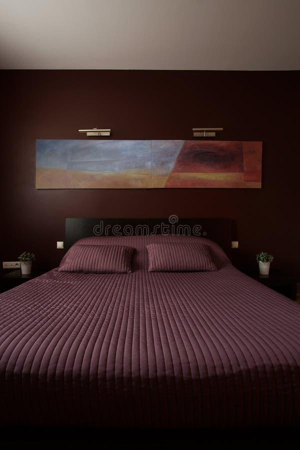 Фиолетовое покрывало на кровати стоковое изображение rf