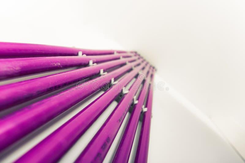 Фиолетовые пластичные трубы системы отопления под полом стоковая фотография
