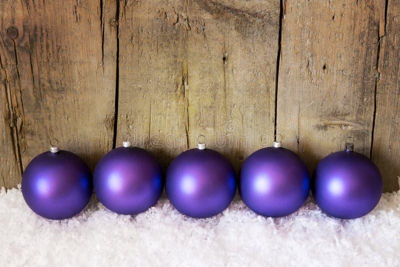Фиолетовые шарики рождества с снегом стоковая фотография