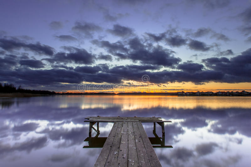 Фиолетовый заход солнца над деревянной молой в спокойном озере стоковые фотографии rf
