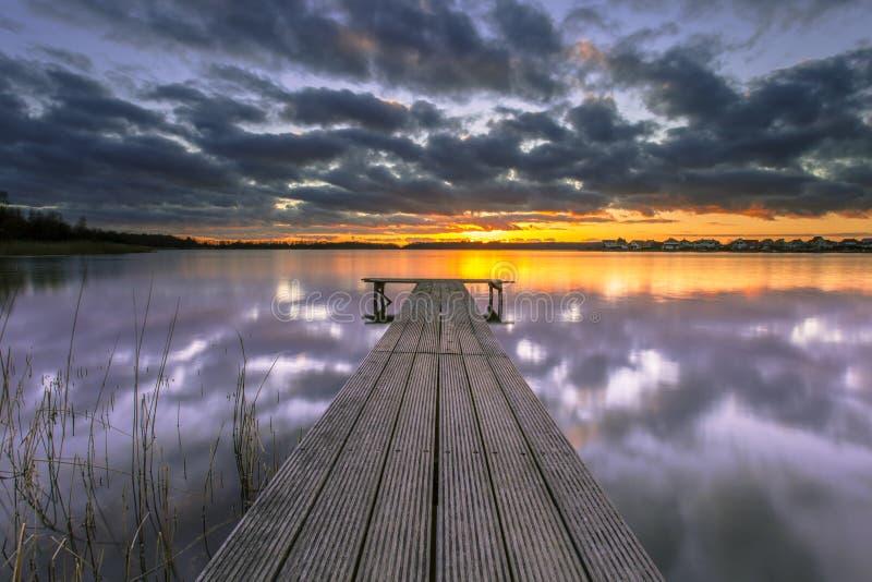 Фиолетовый заход солнца над спокойным озером с деревянной молой стоковые фото