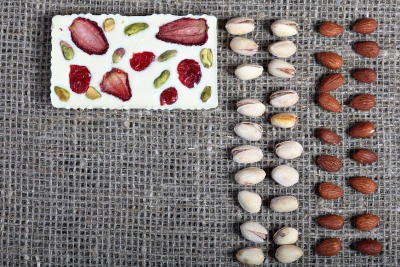 Фисташки и миндалины выровняны вверх в грубой ткани белья Белый шоколад украшенный с сухофруктом стоковые фотографии rf