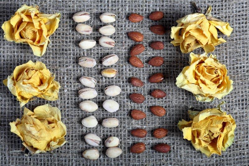 Фисташки и миндалины положены вне в строки на грубую ткань белья Украшенный с высушенными цветками желтых роз стоковые изображения