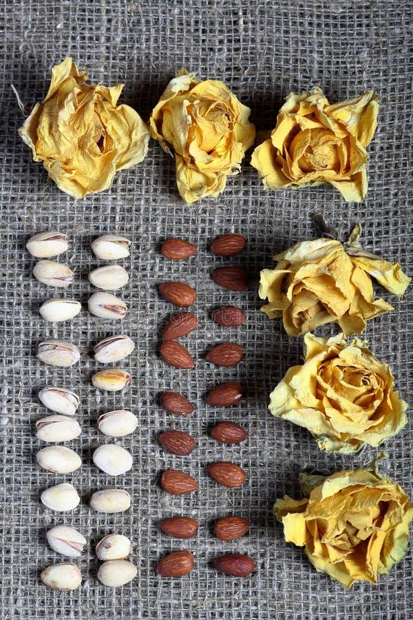 Фисташки и миндалины положены вне в строки на грубую ткань белья Украшенный с высушенными цветками желтых роз стоковые фото