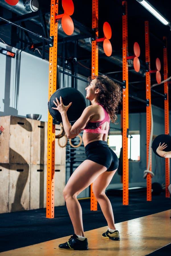 Фитнес и концепция работать - женщина 2 с шариками медицины тренируя в спортзале стоковые фотографии rf