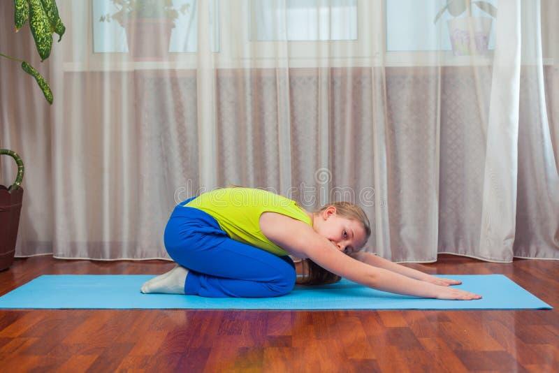 Фитнес концепция спорта, тренировки и образа жизни - ребенок делая тренировки на циновке в доме стоковое изображение