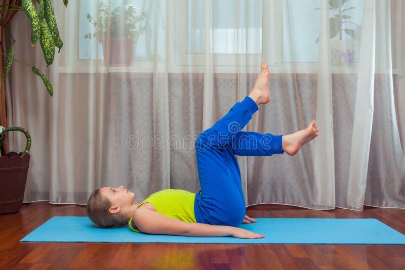 Фитнес концепция спорта, тренировки и образа жизни - ребенок делая тренировки на циновке в доме стоковое изображение rf