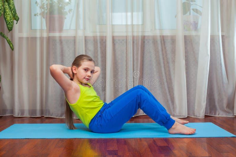 Фитнес концепция спорта, тренировки и образа жизни - ребенок делая тренировки на циновке в доме стоковое фото rf