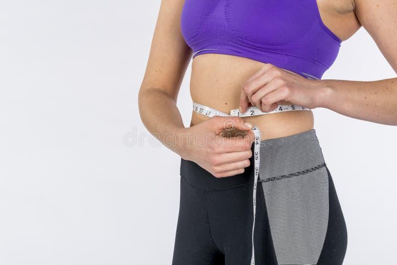 Фитнес-модель Hot Brunette, измеряющая её пояс на белом фоне стоковая фотография rf