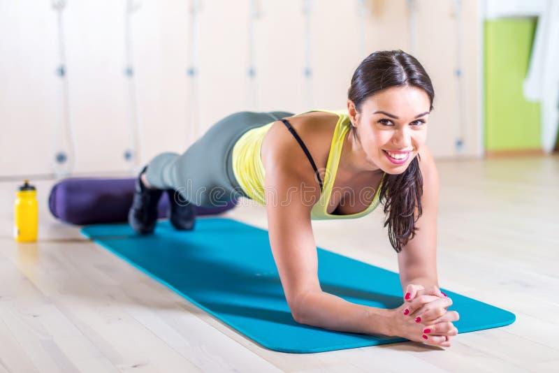 Фитнес портрета тренируя атлетическую sporty женщину делая тренировку планки в концепции спортзала или занятий йогой работая разм стоковое изображение