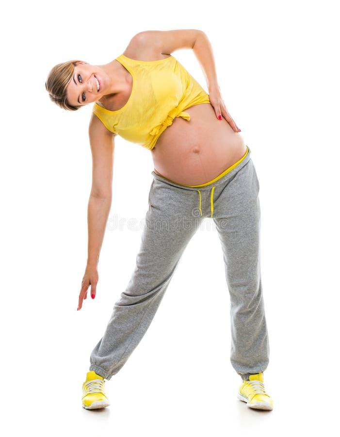 Фитнес приниманнсяый за беременной женщиной стоковое изображение