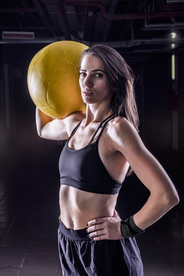 Фитнес резвится женщина держа мягкий шарик медицины внутри помещения стоковая фотография rf