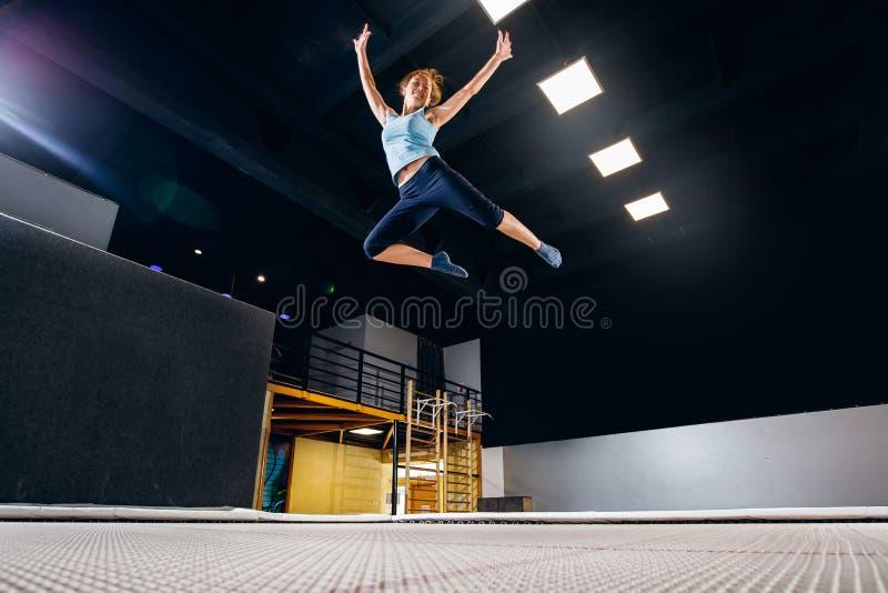 Фитнес спортсмена молодой женщины скача на батут клуба стоковые изображения rf