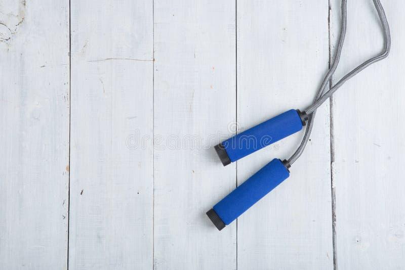 Фитнес/спорт и здоровая концепция образа жизни - скача/прыгая веревочка с голубыми ручками стоковое фото