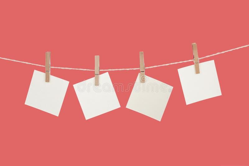 Пустые бумажные карточки вися на зажимках для белья стоковое изображение