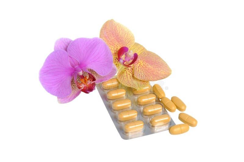 Фильм-покрытые таблетки с 2 цветками орхидеи на сером цвете стоковая фотография rf