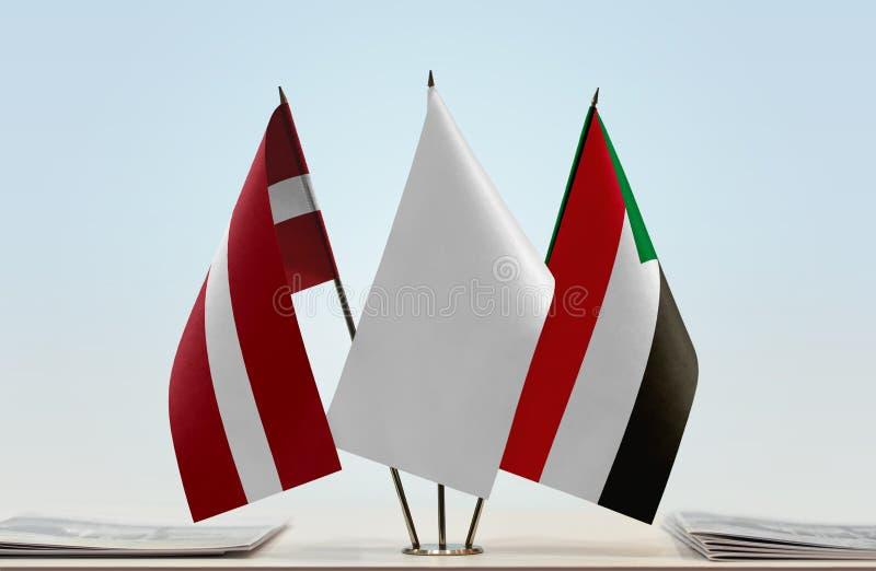 Флаги Латвии и Судана стоковая фотография rf