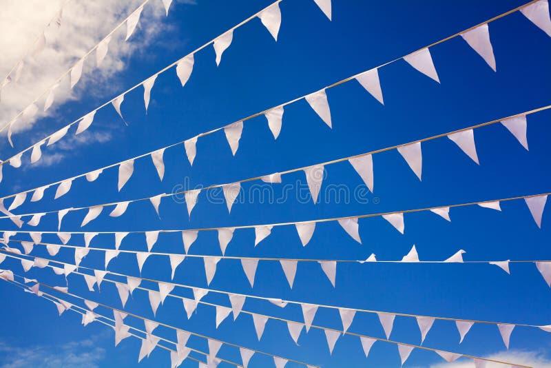 Флаги парламентера развевая в ветре на конце предпосылки голубого неба военно-морского флота вверх, знамена хлопают на ветерке, д стоковое изображение rf