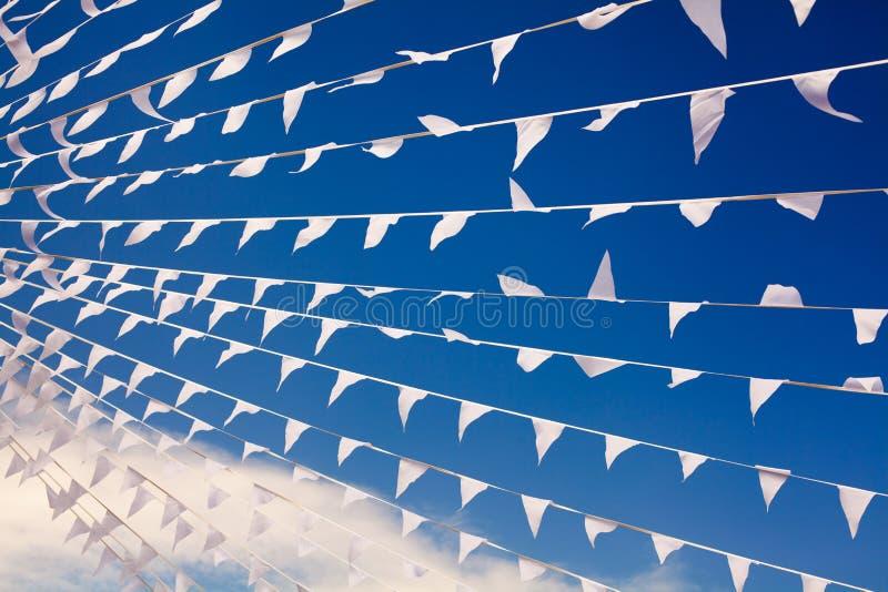 Флаги парламентера развевая в ветре на конце предпосылки голубого неба военно-морского флота вверх, знамена хлопают на ветерке, д стоковое фото