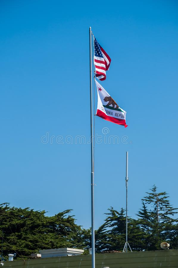 Флаги США и Калифорнии развевая в ветре против яркого голубого неба стоковые изображения rf