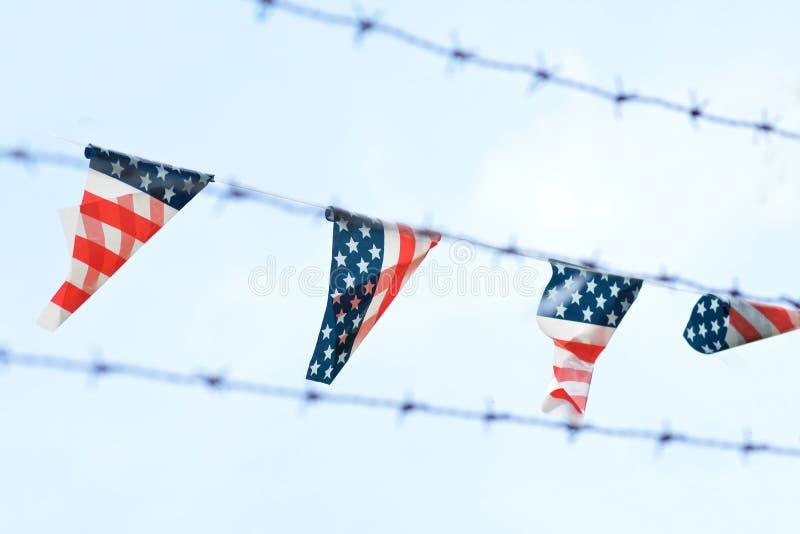 Флаги с американскими цветами с красными нашивками и белыми звездами на голубой предпосылке вися в ряд окруженными колючей провол стоковая фотография rf