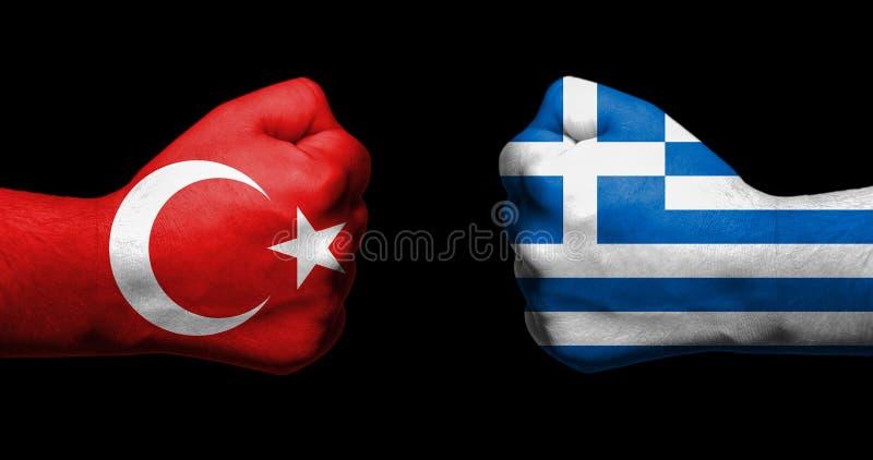 Флаги Турции и Греции покрашенных на смотреть на 2 сжатых кулаков стоковое изображение rf