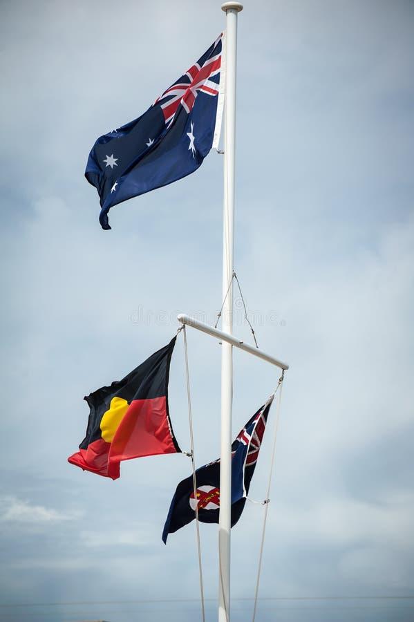 Флагшток летая флаги австралийца, аборигенных и Нового Уэльса стоковые изображения