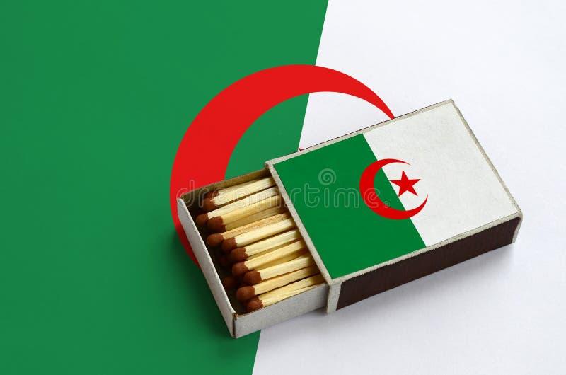 Флаг Алжира показан в открытом matchbox, который заполнен с спичками и лежит на большом флаге стоковая фотография