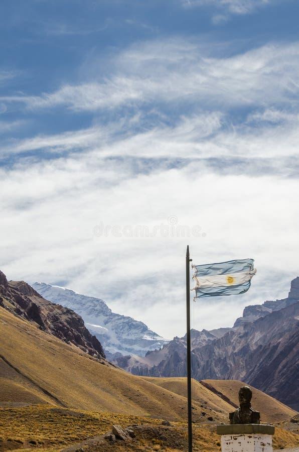Флаг Аргентины развевая с историческими бюстом и горой Аконкагуа позади стоковое фото