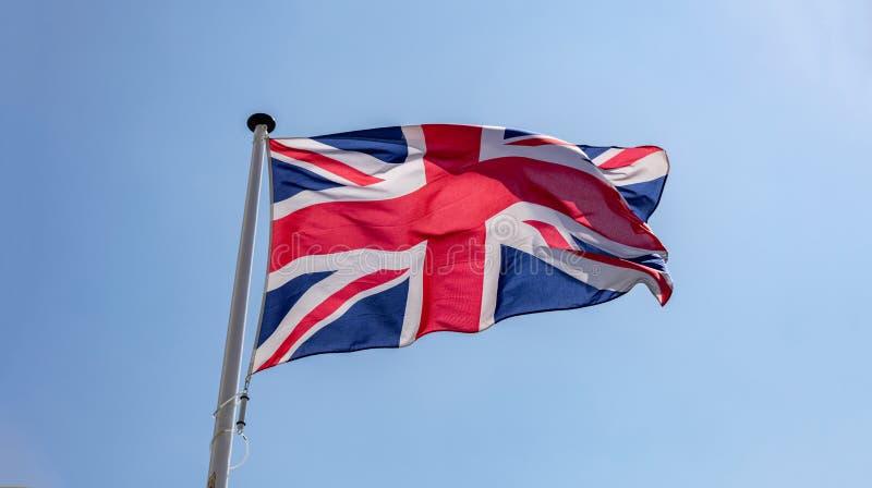Флаг Великобритании развевая против ясного голубого неба стоковое изображение