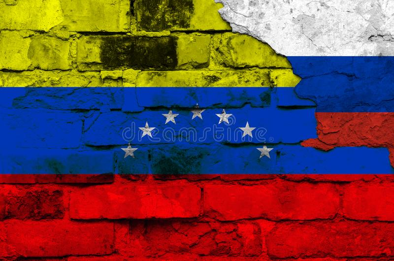 Флаг Венесуэлы и России на предпосылке кирпичной стены со сломленным гипсолитом стоковое изображение rf