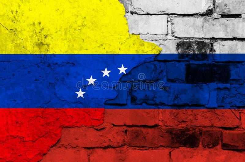 Флаг Венесуэлы и России на предпосылке кирпичной стены со сломленным гипсолитом стоковые фото