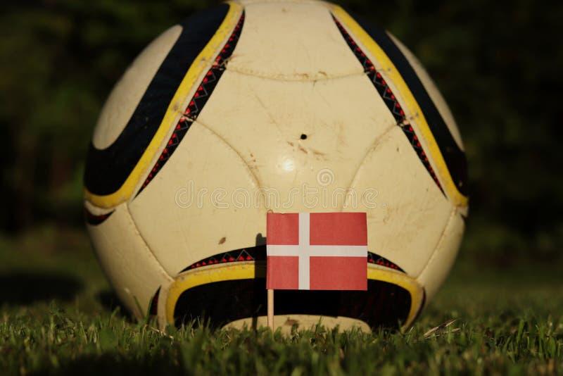 Флаг Дании с травяным и футбольным мячем Чемпионат Европы по футболу 2022 Евро-2020 Символ состояния на поле Флаг Дании стоковое фото
