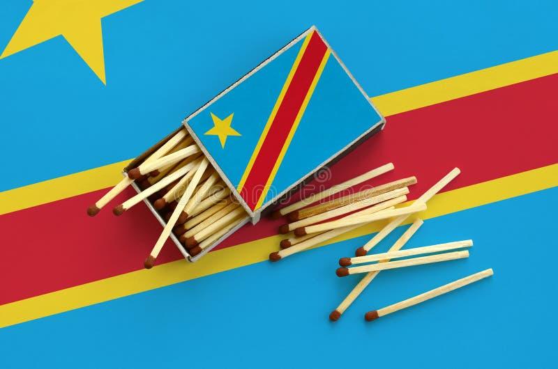 Флаг Демократической Республики Конго показан на открытом matchbox, от которого несколько спичек падают и лож на большом флаге стоковое изображение rf