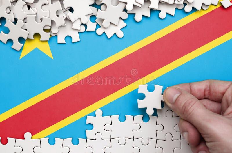 Флаг Демократической Республики Конго показан на таблице на которой человеческая рука складывает головоломку белого цвета стоковые фото