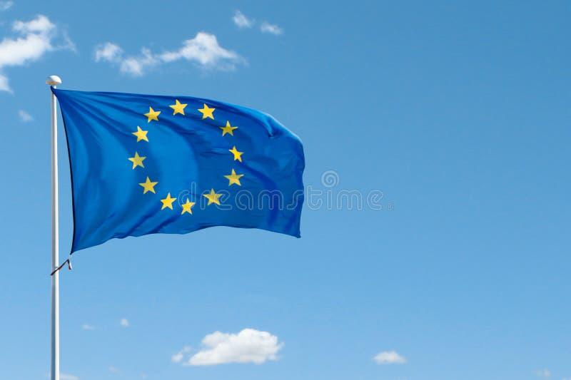 Флаг Европейского союза на флагштоке развевая в воздухе на предпосылке голубого неба стоковое изображение rf