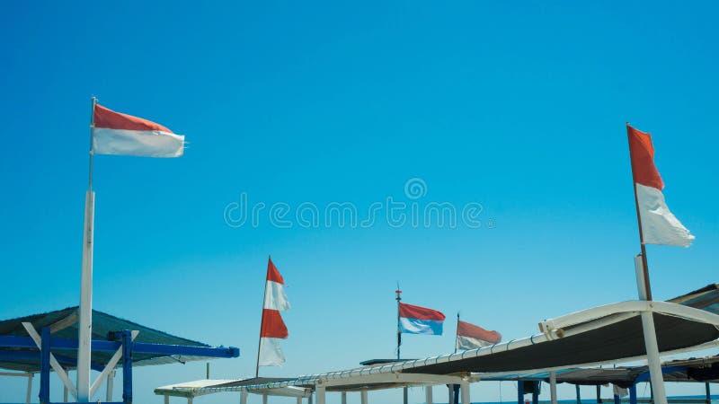 Флаг Индонезии на шлюпке transporation в море с голубым небом и волной стоковые изображения