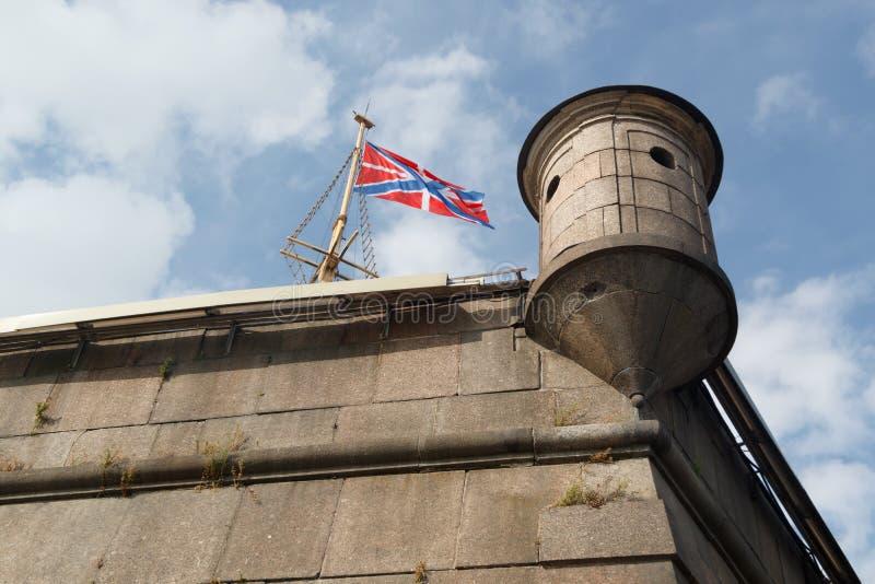 Флаг и башенка на бастионе Naryshkin крепости Питера и Пола на облачном небе предпосылки в Санкт-Петербурге стоковые изображения