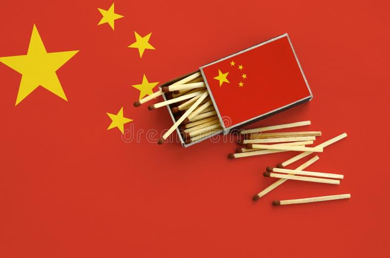 Флаг Китая показан на открытом matchbox, от которого несколько спичек падают и лож на большом флаге стоковое изображение rf