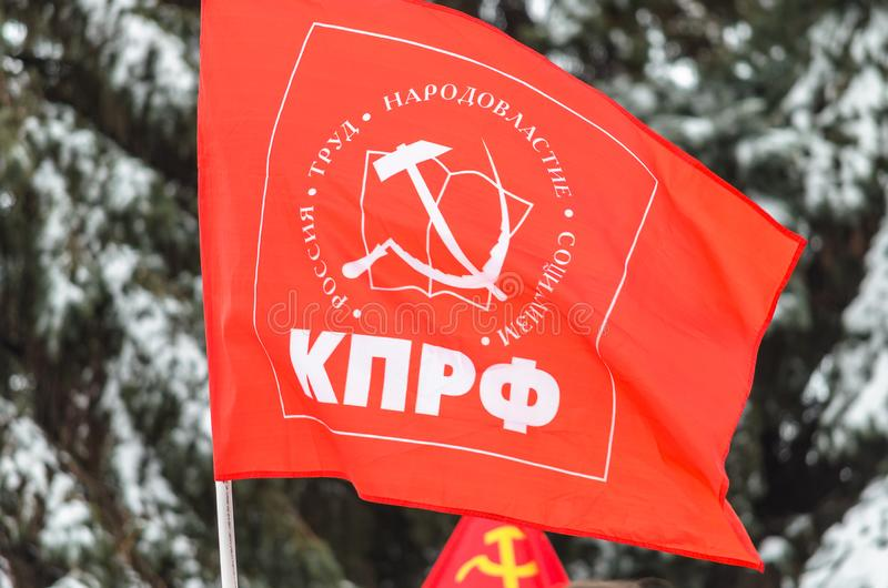 Флаг Коммунистической партии Российской Федерации против фона покрытых снег елей _ стоковые изображения rf