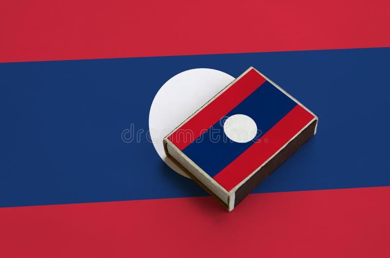 Флаг Лаоса изображен на matchbox который лежит на большом флаге стоковые изображения