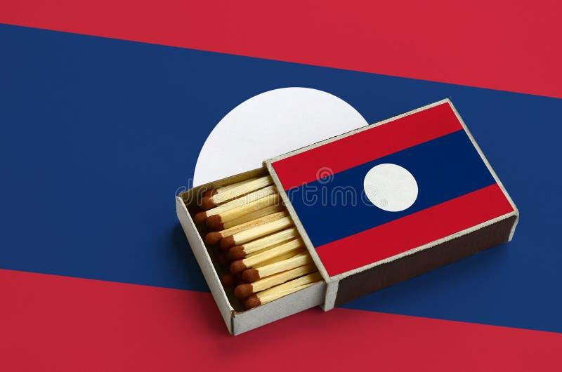 Флаг Лаоса показан в открытом matchbox, который заполнен с спичками и лежит на большом флаге стоковое фото