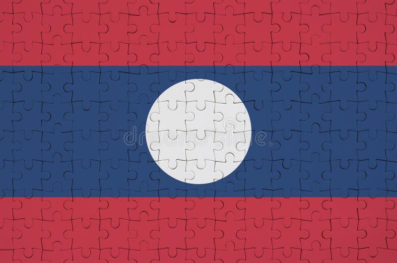 Флаг Лаоса показан на сложенной головоломке стоковое изображение rf