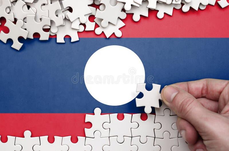 Флаг Лаоса показан на таблице на которой человеческая рука складывает головоломку белого цвета стоковое фото