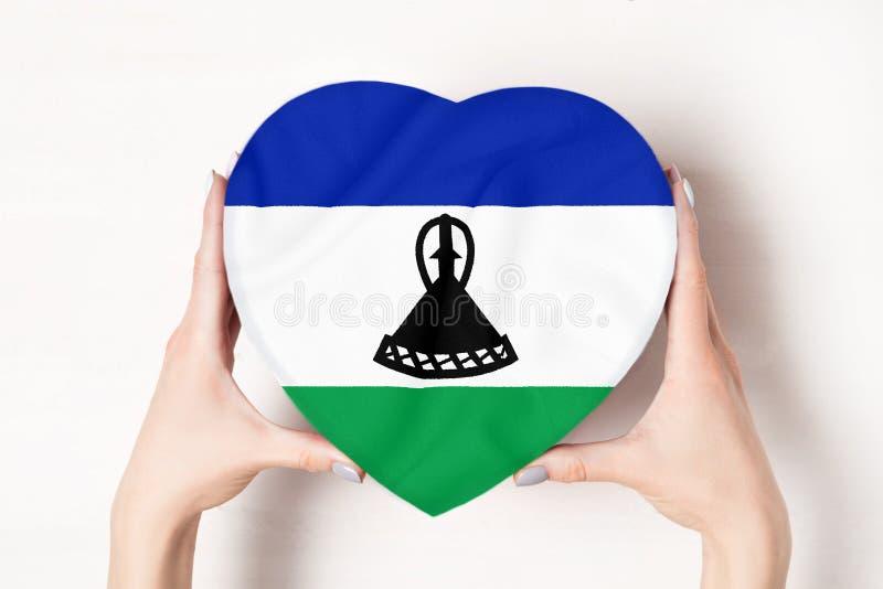 Флаг Лесото на ящике в форме сердца в руках женщины Белый фон стоковое фото