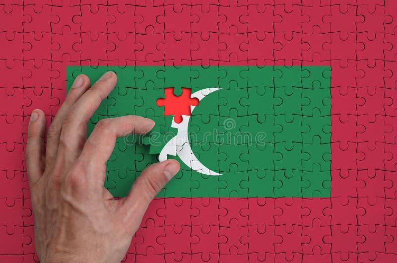 Флаг Мальдивов показан на головоломке, которую рука ` s человека завершает для того чтобы сложить стоковое фото
