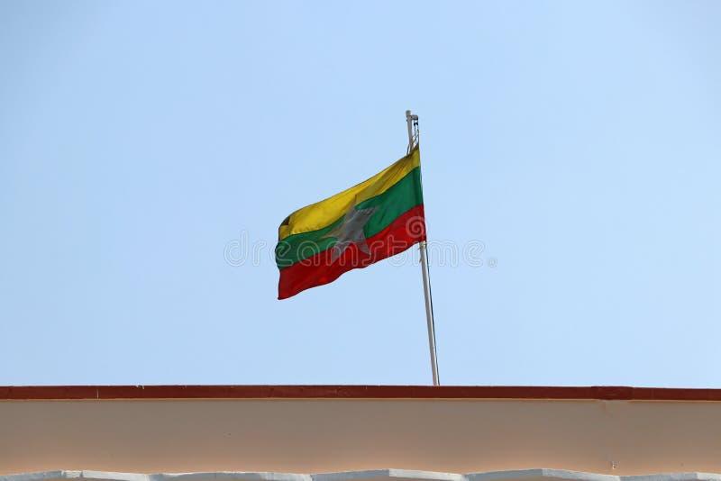 Флаг Мьянмы дунутый ветром на крыше с предпосылкой неба стоковое фото