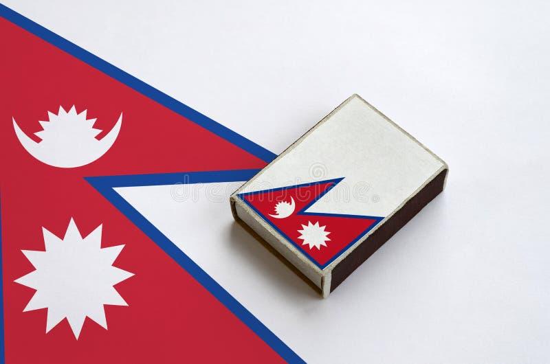 Флаг Непала изображен на matchbox который лежит на большом флаге стоковое фото