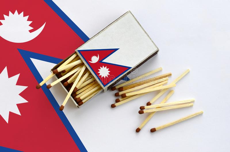 Флаг Непала показан на открытом matchbox, от которого несколько спичек падают и лож на большом флаге стоковые фото